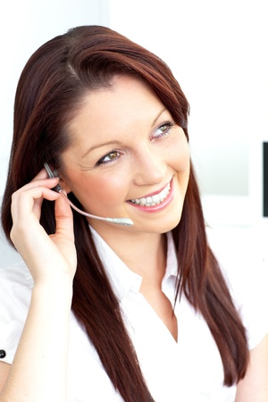 Smiling businesswoman talking on phone using headphones in her office photo