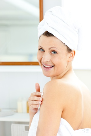 Delighted young woman putting cream on her body looking at the camera  photo
