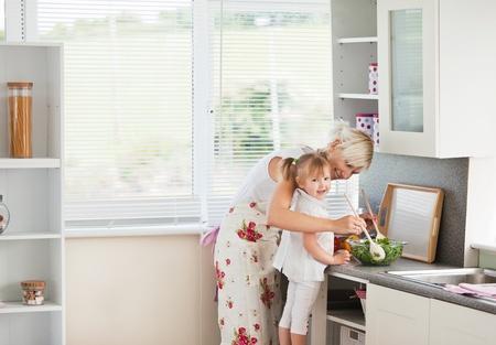 Jolly meisje voorbereiding van een salade met haar moeder