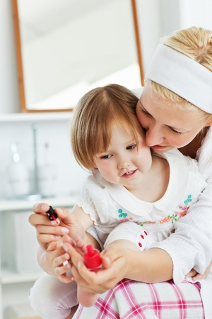 Charming mother making her little daughter Stock Photo - 10131689