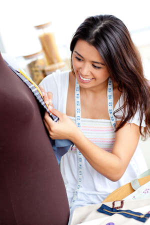 Pretty asian woman sewing clothes in the kitchen  photo