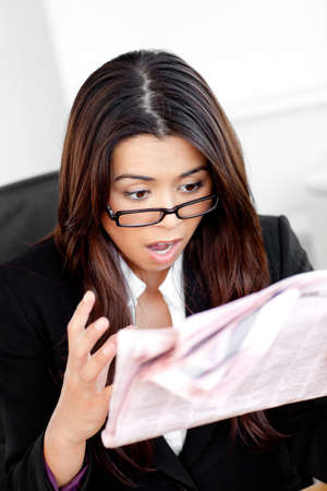 Shocked businesswoman reading a newspaper  photo