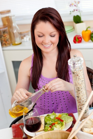 captivating: Bright woman eating a salad with oil in the kitchen Stock Photo
