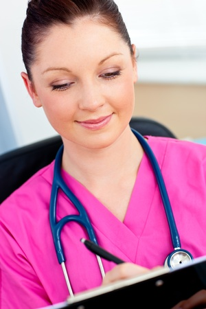 registered nurse: Charming nurse writing on her clipboard