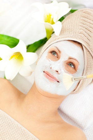 captivating: Captivating young woman receiving white cream on her face