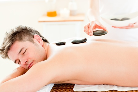 Handsome young man receiving a back massage with hot stones Stock Photo - 10130557