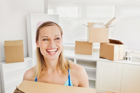 mortage: Radiant woman holding boxes Stock Photo
