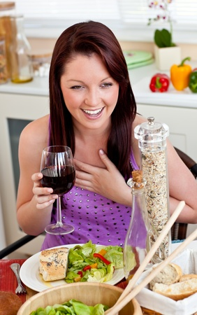 captivating: Delighted woman eating her meal holding a glass of wine at home