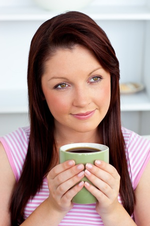 Positive woman holding a cup of coffee at home Stock Photo - 10133312