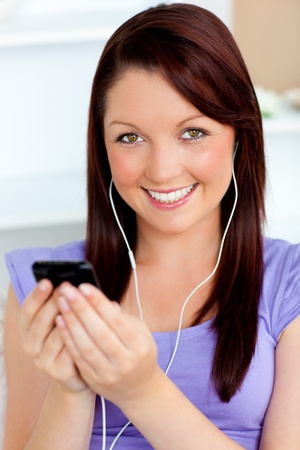 Happy woman using her cellphone to listen to music with earphones photo