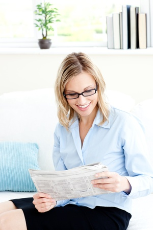 Glowing businesswoman reading newspaper in the office photo