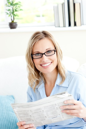 Positive businesswoman reading newspaper in the office photo