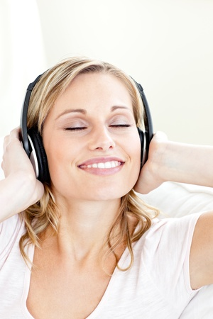 Radiant young woman listening to music wearing headphones photo