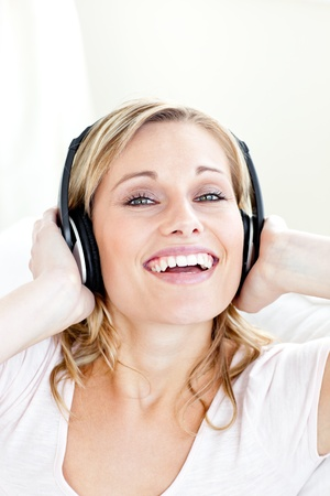 Bright young woman listening to music wearing headphones photo