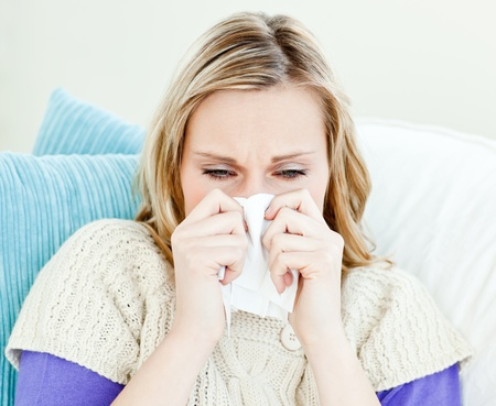feeble: Portrait of a sick pretty woman blowing lying on a sofa
