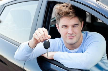 l plate: Charming young man holding a car sitting in his car Stock Photo