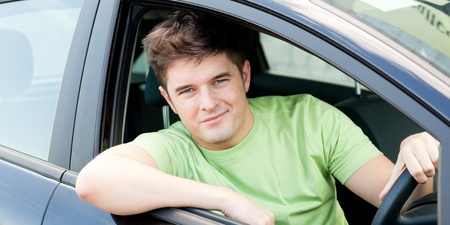 Attractive young man sitting in his car