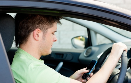distraction: Concentrated man sending a text sitting in his car