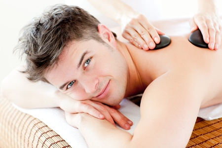 beauty treatment salon: Handsome man receiving a back massage with hot stones