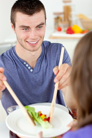 Happy man putting salad on a plate having dinner with his girlfriend in the ktichen photo