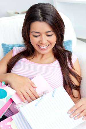 domestics: Happy asian woman with shopping bags sitting on the sofa Stock Photo