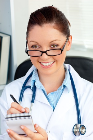 Self-assured female doctor smiling at the camera holding a notepad photo