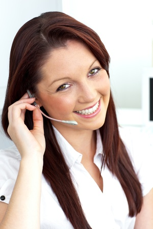Charming young businesswoman wearing headphones smiling at the camera Stock Photo - 10130103