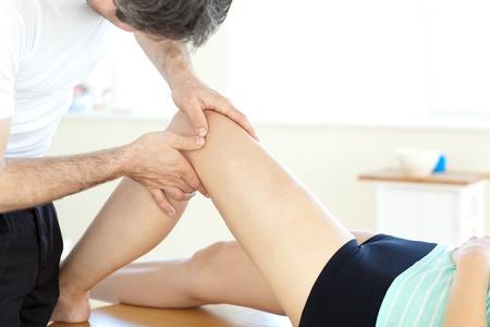 fisico: Apuesto joven fisioterapeuta dando un masaje de piernas Foto de archivo