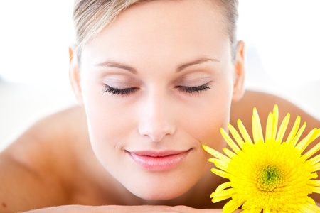 Close-up of a relaxed woman lying on a massage table with a flower photo