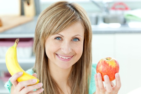 captivating: Positive caucasian woman holing a banana and an apple in the kitchen