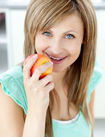 captivating: Captivating caucasian woman eating an apple in the kitchen