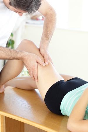 Caucasian woman receiving a leg massage in a health club photo
