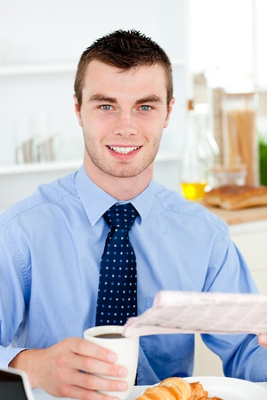 Happy businessman reading the newspaper drinking coffee in the morning at home photo