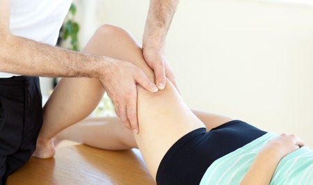strength therapy: Caucasian young physical therapist giving a leg massage
