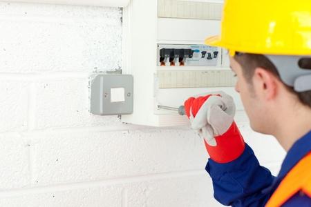 Mature electrician repairing a power plan photo