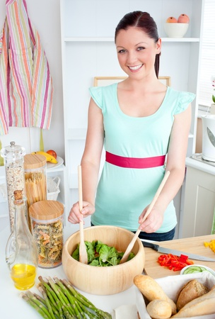 Concentrated young woman preparing a salad in the kitchen Stock Photo - 10131142