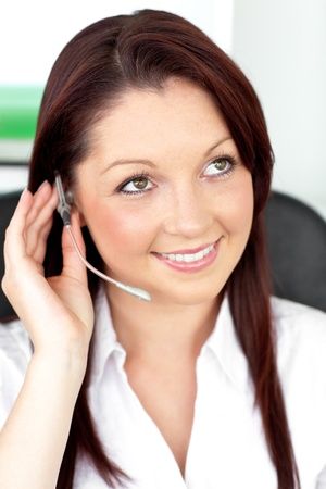 Serious young businesswoman with earpiece in a call center photo