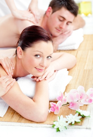 Relaxed young couple receiving a back massage photo