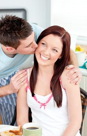 Attentive boyfriend kissing his girlfriend at her cheek during breakfast in the kitchen photo