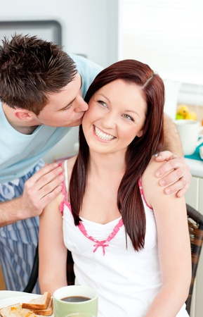 Attentive boyfriend kissing his girlfriend at her cheek during breakfast in the kitchen Stock Photo