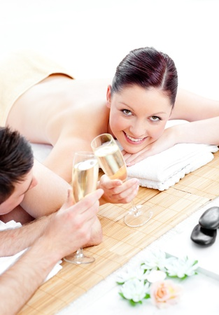 Caucasian young couple lying on a massage table and drinking champagne photo