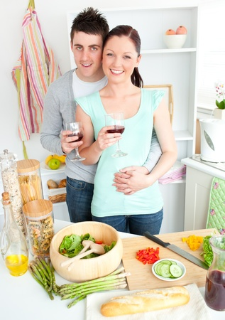 Enamored couple drinking wine in the kitchen Stock Photo - 10131844