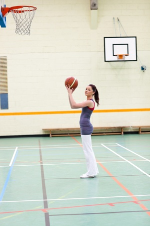 Concentrated woman practicing basketball photo