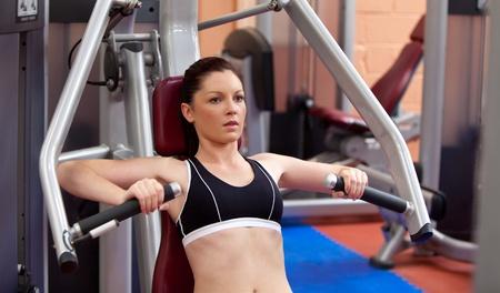 Beautiful athletic woman using a bench press photo