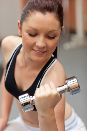 musculation: Portrait of a beautiful woman working out with dumbbells