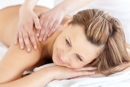 Positive young woman having a back massage in a spa center photo