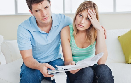 Worried couple after calculating bills sitting in the living-room Stock Photo - 10134151