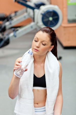Cute athletic woman drinking water after exercises in a fitness centre photo