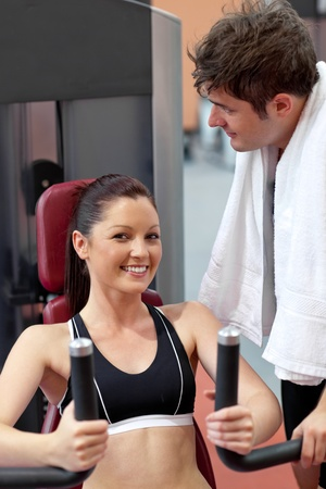 Smiling woman sitting on a bench press with her boyfriend standing next to her Stock Photo - 10133493