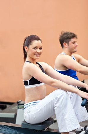 musculation: Athletic young people using a rower in a fitness center Stock Photo